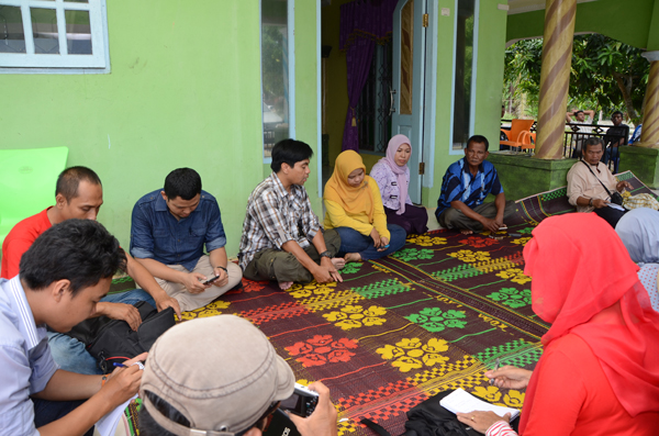 Photo caption: Workshop participants meet Tanjungleban Village Head Haji Atim (blue striped shirt second from right facing camera) on the front veranda of his house June 1 2014. (*)